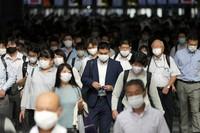 Commuters wearing masks walk in a passageway during a rush hour at Tokyo's Shinagawa Station, on July 12, 2021. (AP Photo/Eugene Hoshiko)