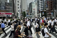 Commuters cross the street during morning rush hour ahead of the 2020 Summer Olympics, on July 13, 2021, in Tokyo. (AP Photo/Jae C. Hong)
