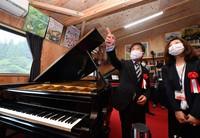 Mitsunori Yagawa, left, guides a guest around the A-bombed piano museum he built on the grounds of his piano workshop in Hiroshima's Asaminami Ward on July 15, 2021. (Mainichi/Naohiro Yamada)