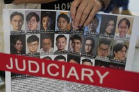 A supporter holds a placard with the photos of some of the 47 pro-democracy defendants outside a court in Hong Kong, on July 8, 2021. (AP Photo/Kin Cheung)