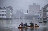 People use rubber rafts in floodwaters after the Meuse River broke its banks during heavy flooding in Liege, Belgium, on July 15, 2021. (AP Photo/Valentin Bianchi)
