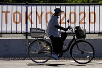 A woman rides her bike past signage for the 2020 Summer Olympics outside of Yumenoshima Park Archery Field, Sunday, July 18, 2021, in Tokyo. (AP Photo/Charlie Riedel)