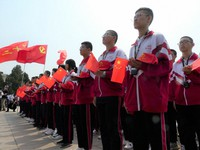 """High school students hold Chinese flags while standing in formation in front of bronzes of Mao Zedong and other """"leaders of the national foundation"""" in Shijiazhuang, China's Hebei province, in this May 2021 file photo. (Mainichi)"""