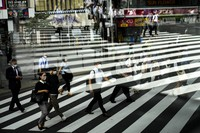 Commuters are reflected in a bus window as they cross the street on July 15, 2021, in Tokyo. (AP Photo/Jae C. Hong)