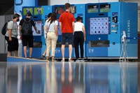Members of news organizations are seen in front of vending machines selling official Tokyo Games goods at the Main Press Center in the capital's Koto Ward on July 17, 2021. (Mainichi/Rei Kubo)