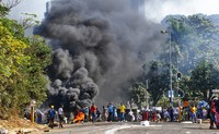 In this July 12, 2021 file photo, looters outside a shopping centre alongside a burning barricade in Durban, South Africa. (AP Photo/Andre Swart)