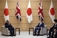 From left, Britain's Defense Secretary Ben Wallace, Japanese Prime Minister Yoshihide Suga and Japanese Defense Minister Nobuo Kishi attend a meeting at the prime minister's office in Tokyo on July 20, 2021. (Franck Robichon/Pool Photo via AP)