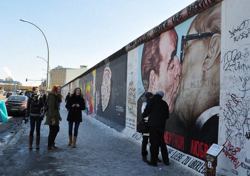 「ベルリンの壁」の一部は、壁に絵が描かれた「イーストサイド・ギャラリー」として残されている。共産主義の結束を示したブレジネフ元ソ連共産党書記長とホーネッカー元東独国家評議会議長の「兄弟のキス」の絵の前は、カップルのキスの名所だ=2013年3月、篠田航一撮影