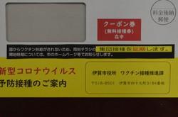 ワクチンの接種券(クーポン券)を入れる封筒に貼られた、集団接種の延期を知らせるシール(見本)=三重県伊賀市役所で