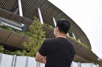 A Vietnamese man looks up at the Japan National Stadium through fences in Shinjuku Ward, Tokyo, in May 2021. (Mainichi/Shunsuke Sekiya)