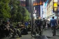 People walk around and gather at a bar after the government imposed 8 p.m. closing times for restaurants and bars under Tokyo's fourth state of emergency on July 17, 2021, in Tokyo. (AP Photo/Kiichiro Sato)