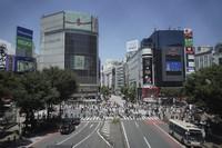 People walk across Tokyo's Shibuya scramble crossing, on July 21, 2021. (AP Photo/Kantaro Komiya)