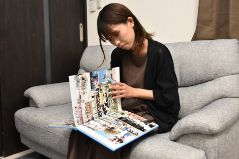 Mai Hirono is seen looking at a photo album from her days as a kindergartner, on July 6, 2021, in Kobe. (Mainichi/Ai Murata)