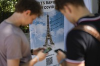 Visitors register for COVID-19 tests at the Eiffel Tower in Paris, Wednesday, July 21, 2021. (AP Photo/Daniel Cole)