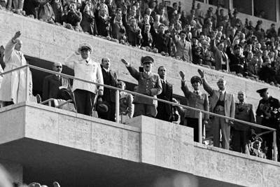 表彰式での国旗掲揚に敬礼をするヒトラー(中央)ら。スタンドの観衆もナチス式の敬礼をしている=ベルリンのオリンピックスタジアムで1936年8月、高田正雄撮影