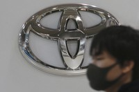 In this Nov. 2, 2020 file photo, a visitor wearing a face mask walks by the logo of Toyota Motor Corp. at its showroom in Tokyo. (AP Photo/Koji Sasahara)