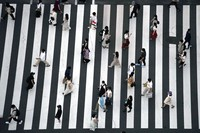 People wearing protective masks to help curb the spread of the coronavirus walk along a pedestrian crossing on July 22, 2021, in Tokyo. (AP Photo/Eugene Hoshiko)