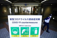 In this July 22, 2021, file photo, security officer passes a sign displaying COVID-19 protocols in the Main Press Center at the 2020 Summer Olympics, in Tokyo, Japan. (AP Photo/John Minchillo)