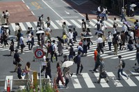 People wearing face masks to help curb the spread of the coronavirus walk across a busy crossing in Tokyo's Shibuya district on Saturday, July 24, 2021, a day after the opening of the Tokyo Olympics. (AP Photo/Kantaro Komiya)