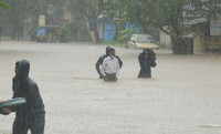 People wade through floodwaters in Kolhapur in the western Indian state of Maharashtra, on July 23, 2021. (AP Photo)