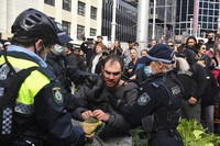 A protester, center, is arrested by police at Sydney Town Hall during a 'World Wide Rally For Freedom' anti-lockdown rally in Sydney, Australia, on July 24, 2021. (Mick Tsikas/AAP Image via AP)