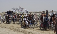 In this July 14, 2021 file photo, supporters of the Taliban carry their signature white flags after the Taliban said they seized the Afghan border town of Spin Boldaka across from the town of Chaman, Pakistan. (AP Photo/Tariq Achkzai)