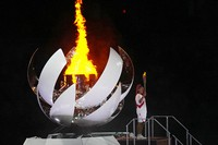 Naomi Osaka stands beside the Olympic flame during the opening ceremony in the Olympic Stadium at the 2020 Summer Olympics, on July 23, 2021, in Tokyo, Japan. (AP Photo/David J. Phillip)