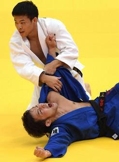 In this Nov. 22, 2019 file photo, Naohisa Takato, blue, reacts after winning the men's 60-kilogram class at a Grand Slam judo event at Maruzen Intec Arena Osaka. (Mainichi)