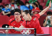 Japan's Mima Ito, right, and Jun Mizutani compete during table tennis mixed doubles against Austria's Sofia Polcanova and Stefan Fegerl at the 2020 Summer Olympics, on July 24, 2021, in Tokyo. (Mainichi/Takehiko Onishi)