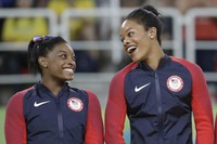 In this Aug. 9, 2016, file photo, U.S. gymnasts and gold medalists, Simone Biles, left and Gabrielle Douglas celebrate on the podium during the medal ceremony for the artistic gymnastics women's team at the 2016 Summer Olympics in Rio de Janeiro, Brazil. (AP Photo/Julio Cortez)