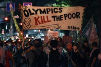Anti-Olympic protestors demonstrate near the National Stadium in Tokyo, Japan where the opening ceremony of the Tokyo Olympics is taking place, on July 23, 2021. (AP Photo/Kantaro Komiya)