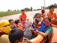 This photograph provided by India's National Disaster Response Force (NDRF) shows NDRF personnel rescuing flood affected women and children at Kolhapur in the western Indian state of Maharashtra, Sunday, July 25, 2021. (National Disaster Response Force via AP)