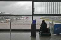 A passenger sits on her luggage watching passenger airplanes parked on the tarmac after all flights were canceled at Pudong International Airport in Shanghai, China, Sunday, July 25, 2021. (AP Photo/Andy Wong)