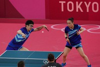 Japan's Mima Ito and Jun Mizutani compete during the table tennis mixed doubles quarterfinal match against Germany's Petrissa Solja and Patrick Franziska at the 2020 Summer Olympics, Sunday, July 25, 2021, in Tokyo. (AP Photo/Kin Cheung)