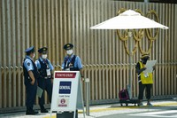 Police officers stand near the entrance to the athlete's village for the 2020 Summer Olympics and Paralympics, Thursday, July 15, 2021, in Tokyo. (AP Photo/Jae C. Hong)