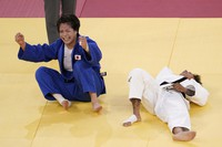 Uta Abe, of Japan, left, celebrates after defeating Amandine Buchard, of France, during a women's -52kg gold medal judo match at the Tokyo 2020 Olympics, July 25, 2021, in Tokyo. (AP Photo/David Goldman)