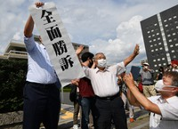 A lawyer for plaintiffs in the lawsuit that ruled hibakusha health handbooks be issued to 84 people exposed to black rain following the atomic bombing of Hiroshima holds up a sign signifying a full victory for the plaintiffs, in Hiroshima's Naka Ward, on July 14, 2021. (Mainichi/Naohiro Yamada)