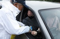 A person preparing to climb Mount Fuji receives a temperature check because they were not carrying a check sheet, at the parking area below the first station on the Fuji Subaru Line, on July 5, 2021. (Mainichi/Satoru Yamamoto)
