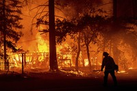 A firefighter passes a burning home as the Dixie Fire flares in Plumas County, Calif., on July 24, 2021. (AP Photo/Noah Berger)