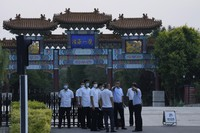 A member of security personnel gestures towards journalists outside the Tianjin Binhai No. 1 Hotel where U.S. and Chinese officials are expected to hold talks in Tianjin municipality in China on July 25, 2021. (AP Photo/Ng Han Guan)