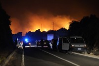 Cars are parked by the road as fires have been raging through the countryside in Cuglieri, near Oristano, Sardinia, Italy, on July 25, 2021. (Alessandro Tocco/LaPresse via AP)