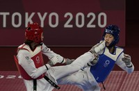 Kimia Alizadeh Zonoozi, Refugee Olympic Team, left, attacks China's Zhou Lijun during the taekwondo women's 57kg match at the 2020 Summer Olympics, on July 25, 2021, in Tokyo, Japan. (AP Photo/Themba Hadebe)
