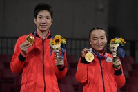 Gold medalists Japan's Mima Ito, left, and Jun Mizutani pose on the podium after winning the table tennis mixed doubles gold medal match against China's Xu Xin and Liu Shiwen at the 2020 Summer Olympics, on July 26, 2021, in Tokyo. (AP Photo/Kin Cheung)
