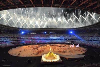 東京オリンピックの開会式で、聖火(手前)の点火とともに打ち上げられる花火=国立競技場で2021年7月23日午後11時49分、徳野仁子撮影