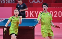 Mima Ito, left, and Jun Mizutani, right, are seen raising their voices after winning a point during their semifinal table tennis mixed doubles match, at the Tokyo Metropolitan Gymnasium on July, 25, 2021, in Tokyo. (Mainichi/Takehiko Onishi)