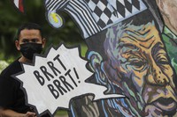 A protester stands beside a caricature of Philippine President Rodrigo Duterte before marching towards the House of Representatives where he is set to deliver his final State of the Nation Address, in Quezon city, Philippines, on July 26, 2021. (AP Photo/Gerard Carreon)
