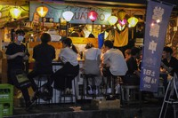People gather at a bar after government imposed 8 p.m. closing time for restaurants and bars under Tokyo's fourth state of emergency on July 17, 2021, in Tokyo. (AP Photo/Kiichiro Sato)