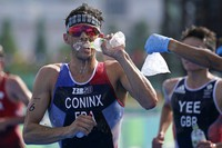 Dorian Coninx of France takes water as a volunteer holds out a bag of ice, during the run portion of the men's individual triathlon at the 2020 Summer Olympics, on July 26, 2021, in Tokyo. (AP Photo/Jae C. Hong)