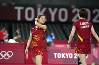 Japan's Yuki Fukushima smiles at teammate Sayaka Hirota during their match against Indonesia's Greysia Polii and Rahayu Apriani celebrate during their women's doubles group play stage badminton match at the Summer Olympics, on July 27, 2021, in Tokyo, Japan. (AP Photo/Markus Schreiber)