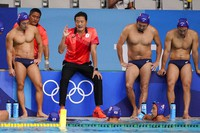 Japan's head coach Yoji Omoto talks with his team during a preliminary round men's water polo match against the United States at the Summer Olympics, on July 25, 2021, in Tokyo, Japan. (AP Photo/Mark Humphrey)